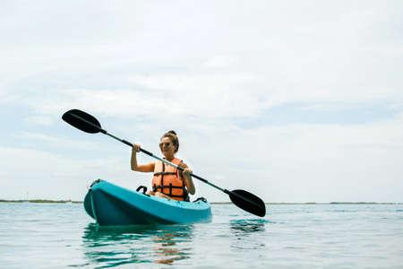 Szczęśliwa młoda i piękna kobieta spływa kajakiem po jeziorze Zdjęcie Seryjne
