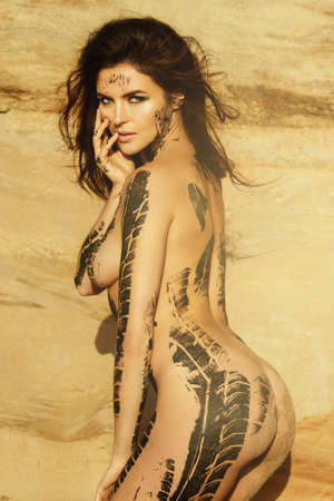 Beautiful naked woman with trace of car tire on her body is posing beside the sand cliffs Imagens