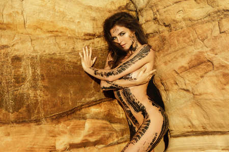 Beautiful naked woman with trace of car tire on her body is posing beside the sand cliffs Foto de archivo