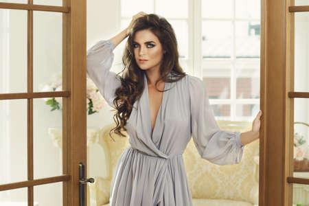 Gorgeous woman in beautiful silk dress standing beside a big doors