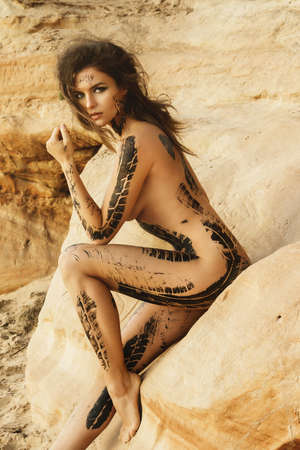 Beautiful naked woman with trace of car tire on her body is posing beside the sand cliffs Stock Photo