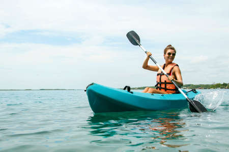 Happy young and beautiful woman kayaking in on the lake