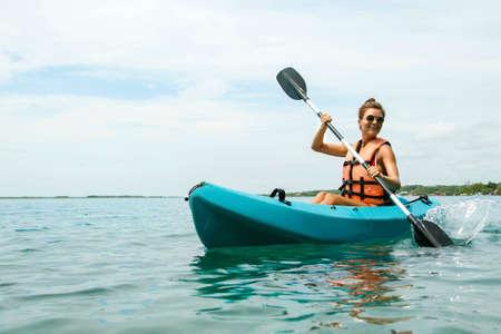 Szczęśliwa młoda i piękna kobieta spływa kajakiem po jeziorze