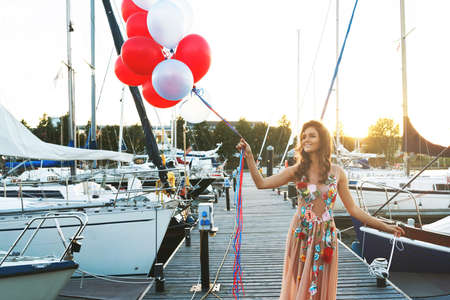 Lovely woman in beautiful dress with a lot of colorful balloons on the yacht pier