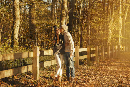 Young couple wearing warm sweaters and woolen hats in the park at sunny autumn day Zdjęcie Seryjne - 133815475