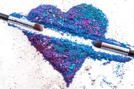 Ombres à paupières écrasées en forme de coeur et pinceaux de maquillage Banque d'images