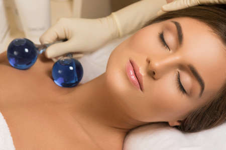 Woman in beauty salon during treatment with a cold glass balls. Face and skin care.