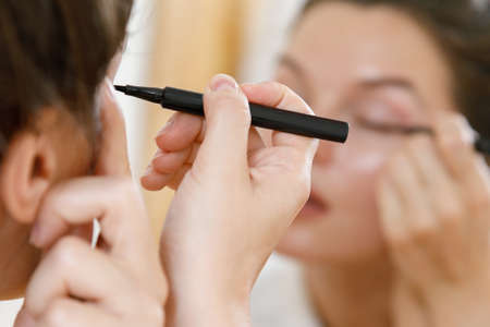 Young woman is applying eyeliner