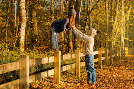 Young couple wearing warm sweaters and woolen hats in the park at sunny autumn day
