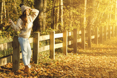 Young woman wearing warm sweater and woolen hat in the park at sunny autumn day