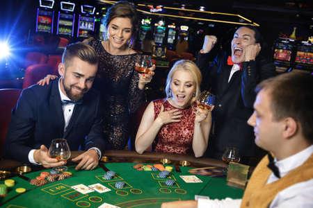 Happy and rich people celebrating successful poker game in the casino Foto de archivo