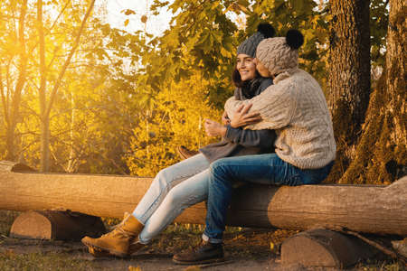Young and happy couple sitting on the bench in autumn park Zdjęcie Seryjne - 133816596