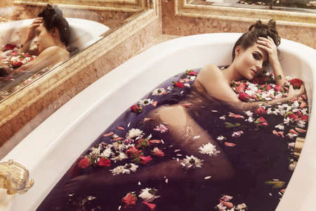 Beautiful woman in the bath with flowers. Rejuvenation and relaxation concept. Foto de archivo