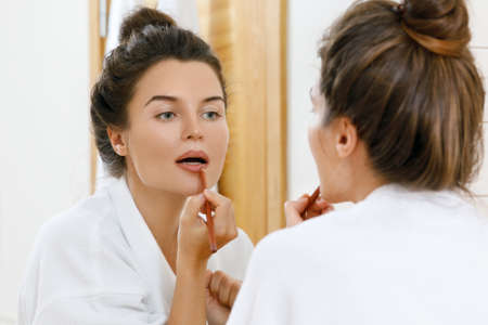 Woman drawing lip contour with a pencil