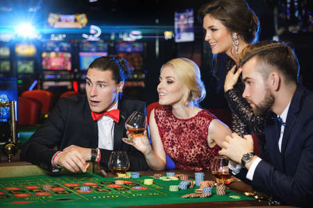 Young, well dressed and rich people playing roulette in the casino Foto de archivo