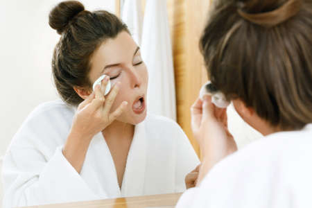 Young woman is removing makeup with a cotton pad Foto de archivo