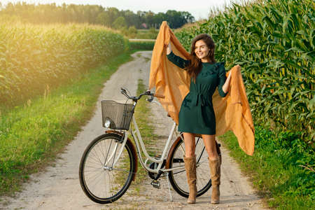 Young happy woman is cycling by the country road in the cornfield Foto de archivo