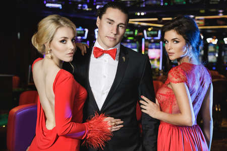 Confident young man and two beautiful women wearing red cocktail dresses in the casino Foto de archivo