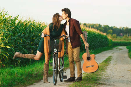 Young couple is walking by country road. Girl riding bicycle and guy is holding guitar.