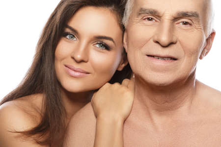 Happy elderly father and his beautiful daughter on white background