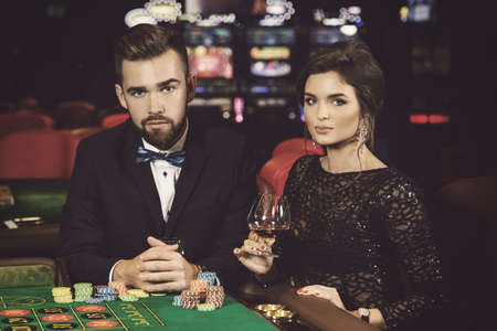 Beautiful and well dressed couple playing roulette in the casino