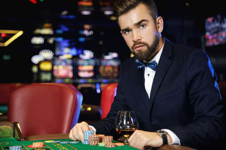 Rich handsome man playing roulette in the casino Foto de archivo