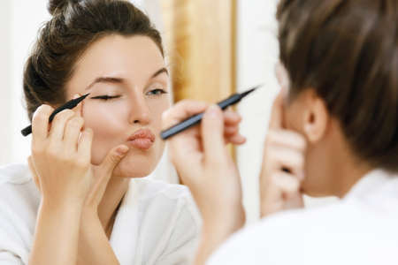 Young woman is disappointed with her skill of applying makeup Foto de archivo