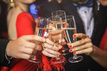 Group of people during celebration. Hands with a full glasses of sparkling wine.