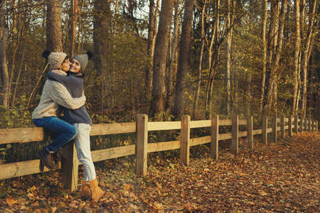 Young couple wearing warm sweaters and woolen hats in the park at sunny autumn day Zdjęcie Seryjne - 133816522