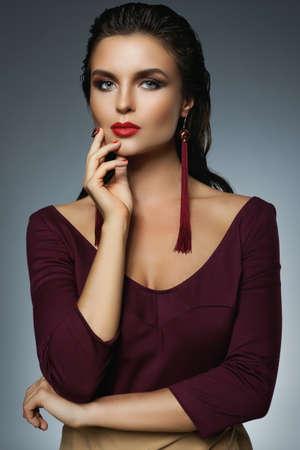 Portrait of stunning woman with a beautiful makeup wearing long red earrings Foto de archivo
