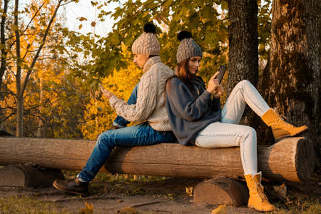 Young and happy couple sitting on the bench in autumn park Foto de archivo