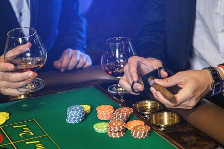 Man is cutting cigar in the casino