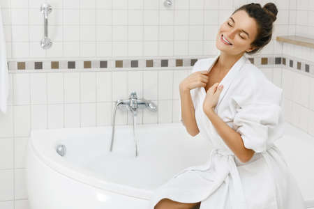 Young woman is preparing to take a bath with a foam
