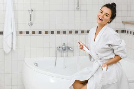 Young woman is preparing to take a bath with a foam Фото со стока - 133672079