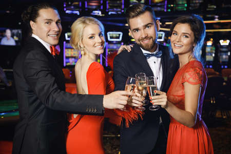 Group of happy people during celebration is drinking sparkling wine in the casino