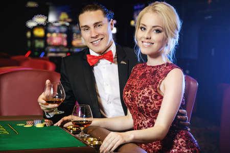 Hermosa pareja bien vestida jugando a la ruleta en el casino