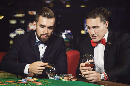 Two rich and handsome guys drinking cognac and playing roulette in the casino Foto de archivo