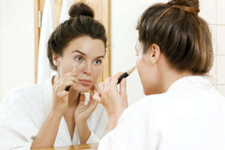 Woman using concealer for under eye circles Stock Photo
