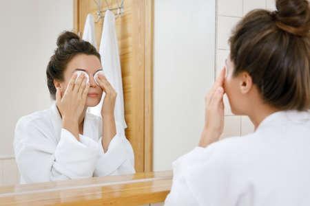 綿パッドで化粧を取り除く女性