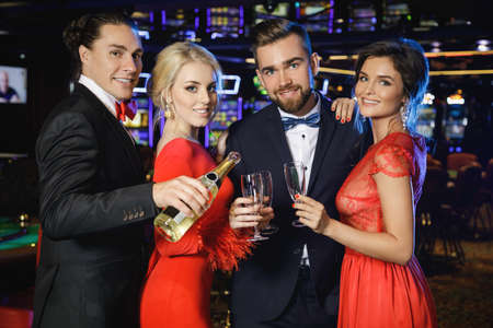 Group of happy people during celebration is drinking sparkling wine in the casino Stock Photo