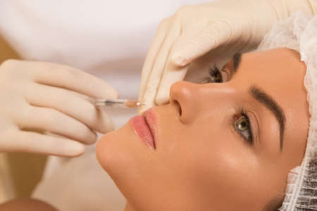 Woman during lips augmentation procedure. Stock Photo