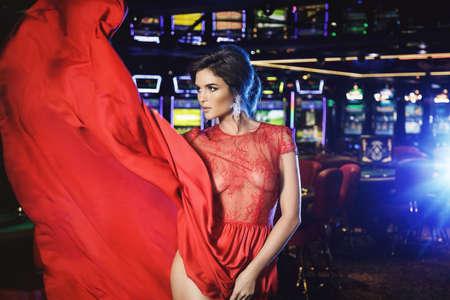Beautiful and sexy woman wearing red dress in the casino Foto de archivo