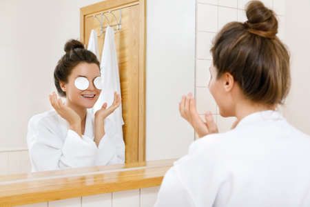 Woman removing makeup with a cotton pads