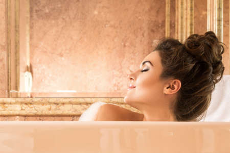 Happy and beautiful woman is taking bath with a foam in luxury apartments