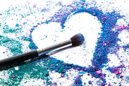 Sombras de ojos trituradas en forma de corazón y pinceles de maquillaje