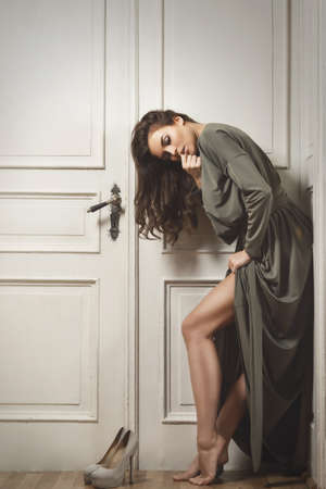 Young and gorgeous woman in beautiful dress is posing beside a big old doors Reklamní fotografie