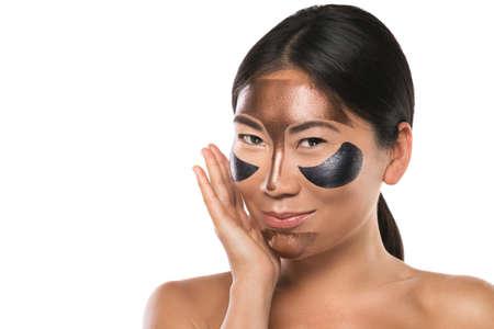 Junge Asiatin mit Peel-off-Maske im Gesicht. Isoliert auf weißem Hintergrund. Standard-Bild