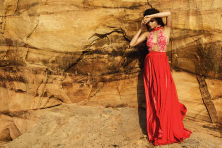 Beautiful sensual woman wearing luxury red dress and posing beside the sand cliffs