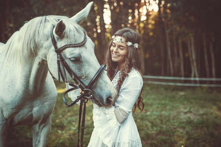 Young woman in beautiful white dress and her beautiful horse
