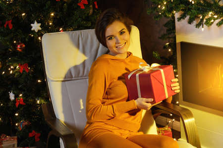 Christmas or New Year celebration. Happy woman sitting in the rocking chair beside fireplace.